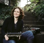 Photo of Mary Robinette Kowal, sitting outdoors on stone steps with a typewriter on her lap