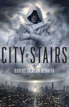 Cover for City of Stairs by Robert Jackson Bennett. A grey, hooded figure looms in a cloudy sky. Below him is a city at night, full of skyscrapers and lighted windows.