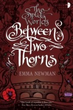 "Cover for Between Two Thorns by Emma Newman. A dark red cover with ""The Split Words"" in smaller gray words atop, and ""Between Two Thorns"" in fancy big white text in the center. Below is an aqueduct with a gate, illustrated in black ink. Black ink filigree climbs either side of the cover, with flowers, bottles, eyes?, gargoyles???"