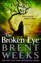 Cover for The Broken Eye by Brent Weeks. A lone man in a hooded cloak stands silhouetted on a hill by a dead, twisted tree full of crows. The sky is a kaleidoscope of orange, yellow, and green.