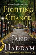 cover for Fighting Chance by Jane Haddam. View down a pretty city sidewalk of paving stones, with trees and iron lamposts on either side. Yellow police tape slashes through the serene scene, trailing into the foreground.