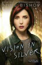 Cover for Vision in Silver by Anne Bishop. A white woman with black hair streaked with red looks at the reader, wearing a jean jacket and with bright yellow light shining behind her.