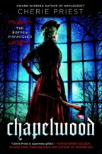 Cover for Chapelwood by Cherie Priest. An older Lizzie Borden stands looking out a darkened window in a dark purple gown, holding a bloody ax.